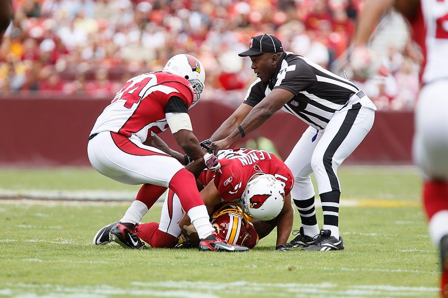 Umpire Ruben Fowler tries to pull Arizona Cardinals' linebacker Paris Lenon (51) off of Redskins' running back, and former teammate, Tim Hightower, after Hightower threw a late block in the first quarter at FedEx Field in Landover, Md., on Sunday, September 18, 2011. (T.J. Kirkpatrick/The Washington Times)