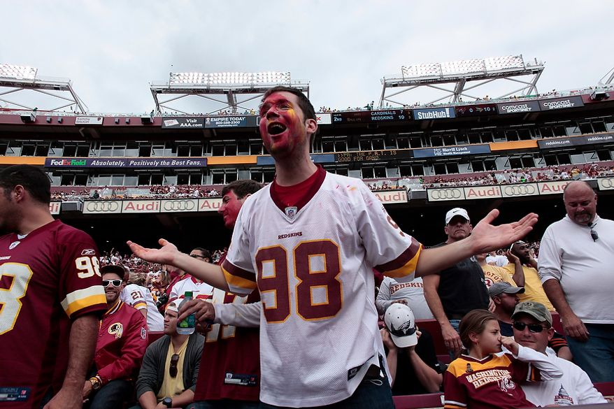 A Redskins fan reacts as Arizona Cardinals' quarterback Kevin Kolb (4) celebrates with wide receiver Larry Fitzgerald after they connected for a 73-yard touchdown pass to start the fourth quarter at FedEx Field in Landover, Md., on Sunday, September 18, 2011.  (T.J. Kirkpatrick/The Washington Times)
