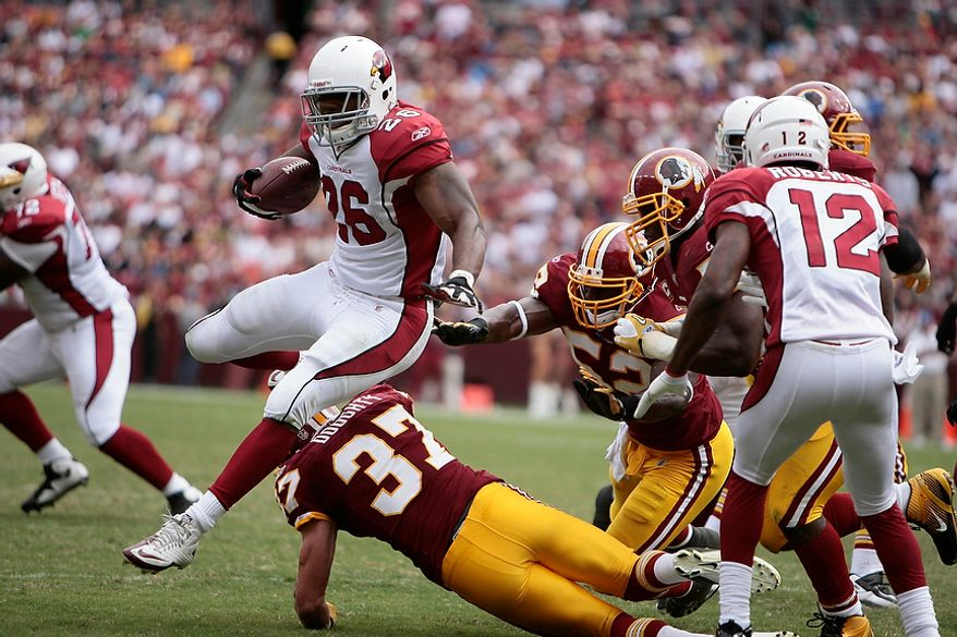 Arizona Cardinals' running back Beanie Wells (26) scampers 2 yards over Redskins' safety Reed Doughty (37) for a third-quarter touchdown at FedEx Field in Landover, Md., on Sunday, September 18, 2011. (T.J. Kirkpatrick/The Washington Times)