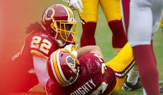 Washington Redskins CB Kevin Barnes (22) and Safety Reed Doughty (37) come up with what eventually was deemed a fumble after the call was reversed late in the fourth quarter against the Arizona Cardinals at FedEx Field in Landover, Md., on Sunday, Sept. 18, 2011. (Andrew Harnik/The Washington Times)