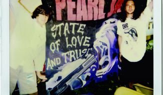 Vinyl Films photographs Director Cameron Crowe (left) and Eddie Vedder unfurl a Pearl Jam flag in Italy in 1993.