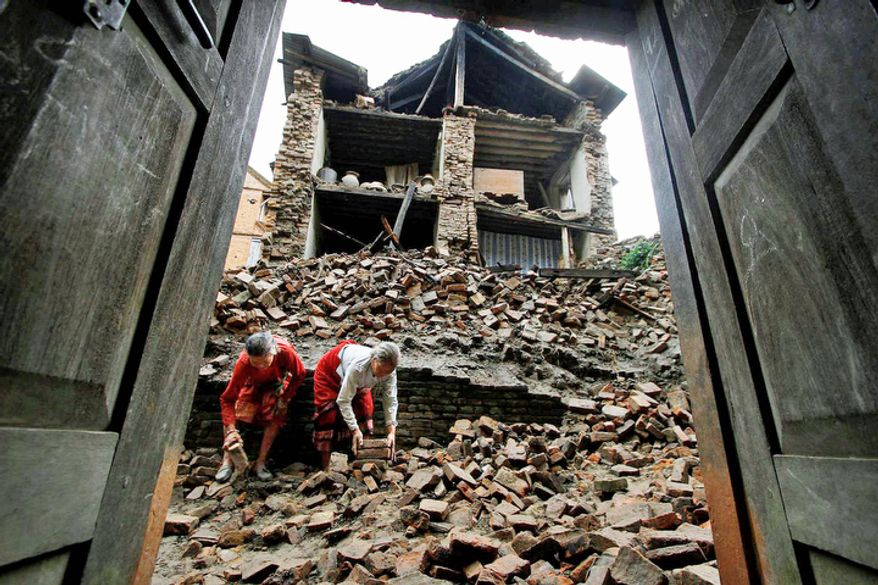 Women in Katmandu, Nepal, remove bricks from a damaged house on Monday, Sept. 19, 2011, to make way for pedestrians after a magnitude-6.9 earthquake shook northeastern India, Nepal and Tibet on Sunday night. (AP Photo/Niranjan Shrestha)