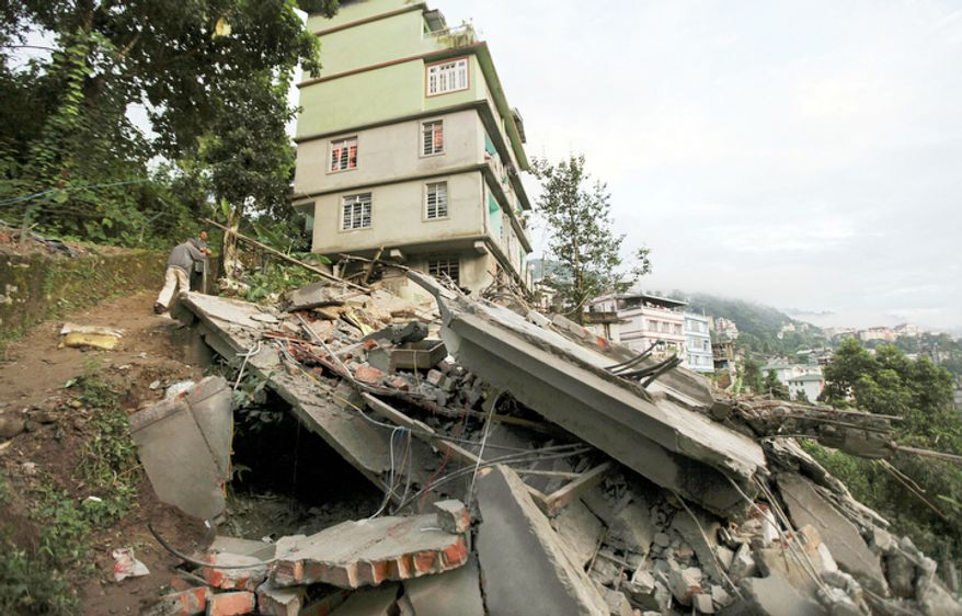 Residents on Monday, Sept. 19, 2011, stand near the debris of a building that collapsed following an earthquake in Gangtok, India. (AP Photo/Altaf Qadri)