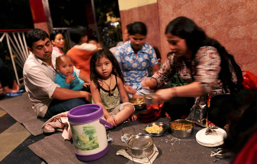 A family eats dinner on Monday, Sept. 19, 2011, after taking shelter in a Hindu temple in fear of more aftershocks following Sunday's earthquake in Gangtok, India. (AP Photo/Altaf Qadri)