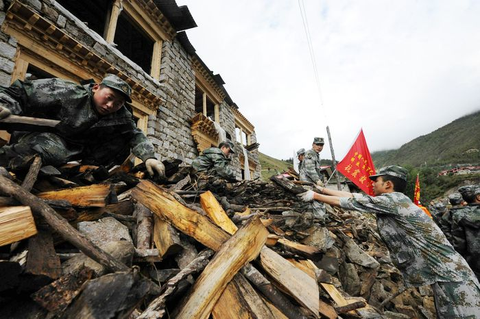 Soldiers clean up a quake-hit house in Yadong County in southwest China's Tibet Autonomous Region on Monday, Sept. 19, 2011. At least seven people have died in the county after Sunday's strong temblor. (AP Photo/Xinhua, Wen Tao)