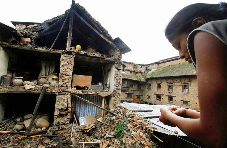 A Nepalese woman looks out of a window at debris of collapsed buildings damaged by Sunday's earthquake in Katmandu, Nepal, on Monday, Sept. 19, 2011. (AP Photo/Niranjan Shrestha)