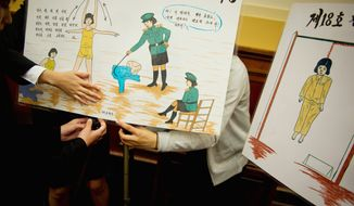 "ROD LAMKEY JR./THE WASHINGTON TIMES Young women prepare posters depicting nightmarish labor-camp conditions to show at a House Foreign Affairs subcommittee hearing Tuesday titled ""Human Rights in North Korea: Challenges and Opportunities."""