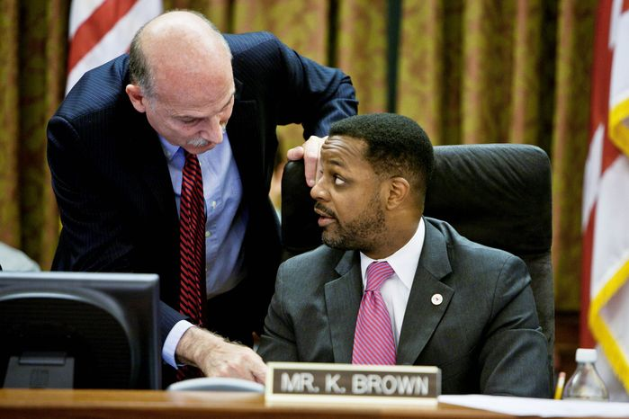 D.C. Council member Phil Mendelson confers with council Chairman Kwame R. Brown on Tuesday.  Mr. Mendelson favored the income-tax increase; Mr. Brown opposed it. (T.J. Kirkpatrick/The Washington Times)