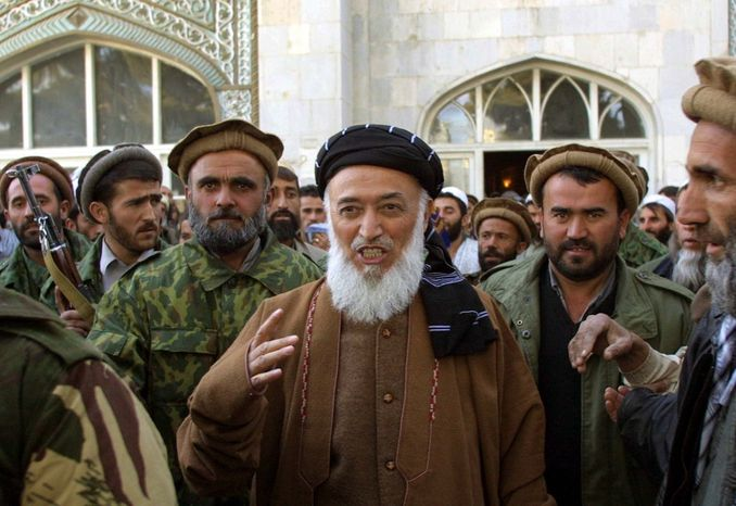 ** FILE ** This Friday, Nov. 23, 2001, file photo shows former Afghan President Burhanuddin Rabbani as he emerges from the Pul-e-Khishti mosque after Friday prayers, surrounded by United Front bodyguards and supporters, in the capital Kabul, Afghanistan. A Kabul police official said Tuesday, Sept. 20, 2011, that Mr. Rabbani was killed by a suicide bomber who had explosives in his turban. (AP Photo/Brennan Linsley)