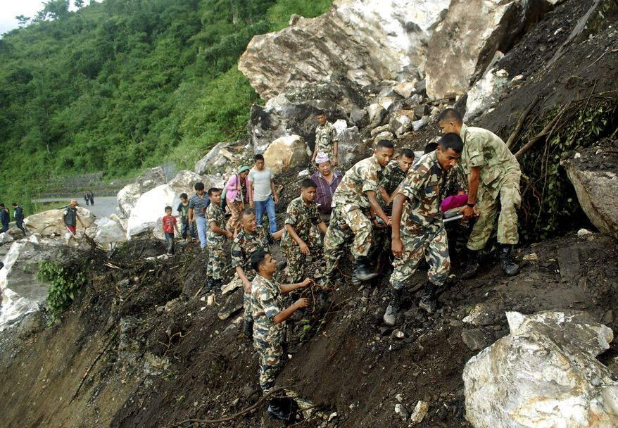 Nepalese soldiers on Monday, Sept. 19, 2011, carry an injured civilian over an area near Dharan in the Dhankuta district of eastern Nepal that was hit by a landslide following a magnitude-6.9 earthquake on Sunday. (AP Photo/Sita Mademba)