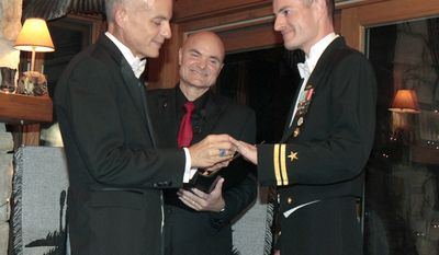 "**FILE** Navy Lt. Gary Ross (right) and Dan Swezy exchange wedding vows early on Sept. 20, 2011, in Duxbury, Vt., at the first possible moment after the formal repeal of the military's ""don't ask, don't tell"" policy. Justice of the Peace Greg Trulson (center) officiated. (Associated Press)"