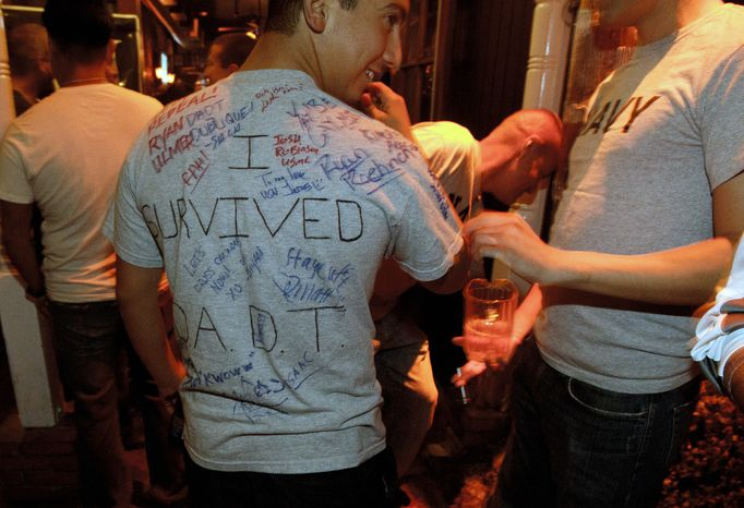 """** FILE ** A man who is active-duty in the Navy, and only gave his name as Matt, wears a shirt being signed by others that reads """"I survived D.A.D.T."""" (don't ask, don't tell) shortly before midnight during a celebration for the end of the policy on Sept. 19, 2011, in a bar in San Diego. (Associated Press)"""