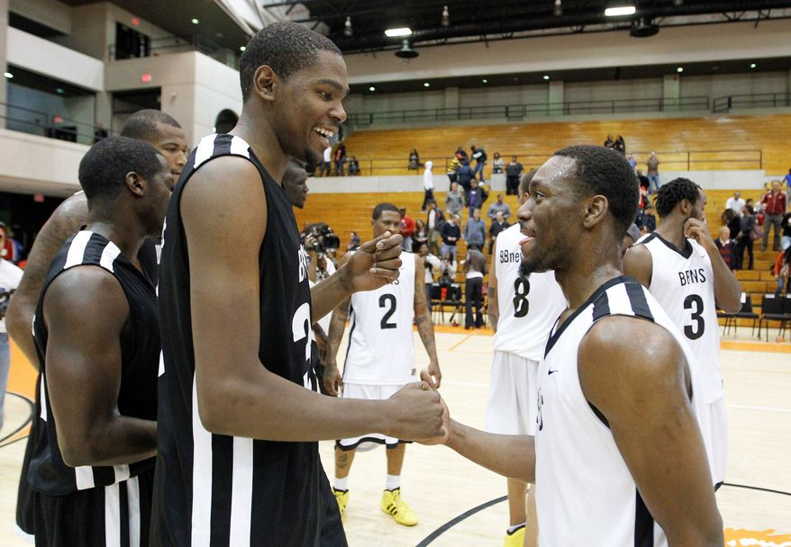 Two-time NBA scoring champion Kevin Durant (left) of Oklahoma City shares a light moment with Charlotte rookie Kemba Walker at a summer-league all-star game at Coolidge High School. (Associated Press)