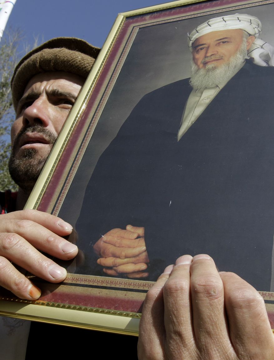 A man holds a poster of former Afghan President Burhanuddin Rabbani, the High Peace Council leader who was assassinated Tuesday, during a rally in Kabul, Afghanistan, on Wednesday, Sept. 21, 2011. (AP Photo/Kamran Jebreili)