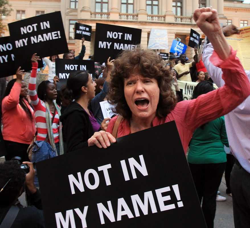 Shelley Serdahely, of Roswell, Ga., joins hundreds of protesters on Sept. 20, 2011, at the Georgia State Capitol in Atlanta against the execution of Troy Anthony Davis, who was convicted of murdering an off-duty Savannah police officer in 1989. (Associated Press/Atlanta Journal & Constitution)