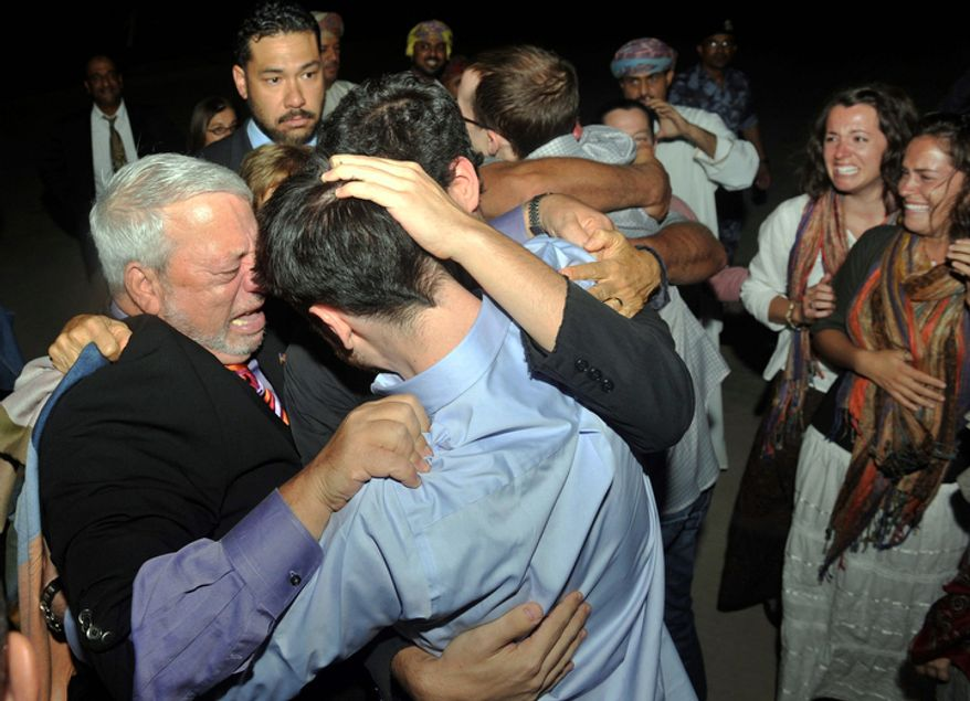 Freed American Josh Fattal (center, in blue shirt) is hugged by relatives and friends upon his arrival in Muscat, Oman, from Iran on Wednesday, Sept. 21, 2011. After more than two years in Iranian custody, Mr. Fattal and Shane Bauer, convicted as spies, took their first steps toward home Wednesday as they bounded down from a private jet and into the arms of family for a joyful reunion in the Gulf state of Oman. (AP Photo/Sultan Al-Hasani)