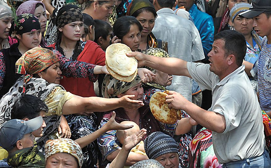 **FILE** Uzbek emergency workers and volunteers pass traditional flat bread to ethnic Uzbek refugees from Kyrgyzstan near the Uzbek village of Jalal-Kuduk on June 14, 2010. (Associated Press)