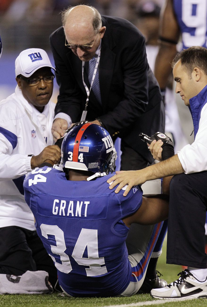 New York Giants defensive back Deon Grant is helped up by trainers during the first quarter of an NFL football game against the St. Louis Rams on Monday, Sept. 19, 2011, in East Rutherford, N.J. (AP Photo/Julio Cortez)