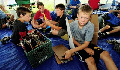 """Associated Press Sixth-grader Colin Green, 11, grabs a clipboard for his next class Sept. 13 inside a tent """"classroom"""" at Moretown, Vt., Elementary School. Flooding damage was estimated at more than $300,000."""