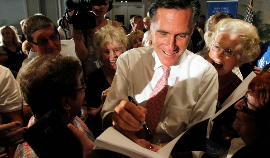 Mitt Romney talks to a supporter after a town-hall meeting in Miami on Wednesday. He discussed his plans to improve the economy and create jobs. (Associated Press)