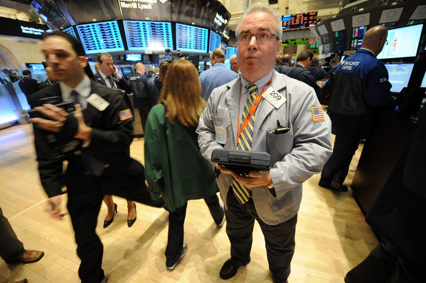Associated Press photographs Trader James Dresch works on the floor Thursday of the New York Stock Exchange. Financial indicators showed investors are quickly losing hope that the economy can keep growing.