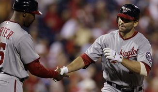 Washington Nationals' Danny Espinosa greets third base coach Bo Porter after hitting a two-run home run off Philadelphia Phillies starting pitcher Vance Worley during the sixth inning Wednesday, Sept. 21, 2011, in Philadelphia. Washington won 7-5. (AP Photo/Matt Slocum)