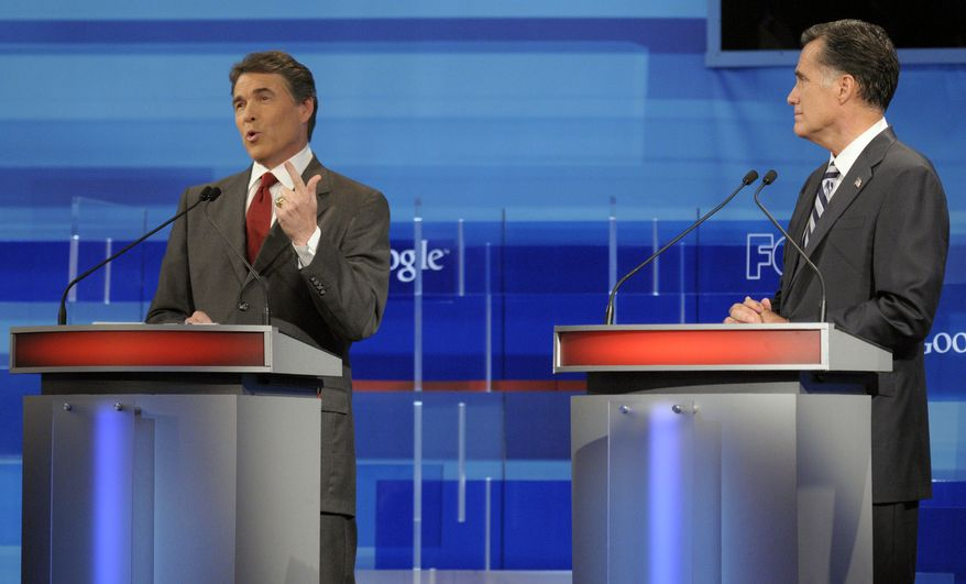 Texas Gov. Rick Perry (left) makes a statement as former Massachusetts Gov. Mitt Romney listens during a Republican presidential candidate debate on Sept. 22, 2011, in Orlando, Fla. (Associated Press)