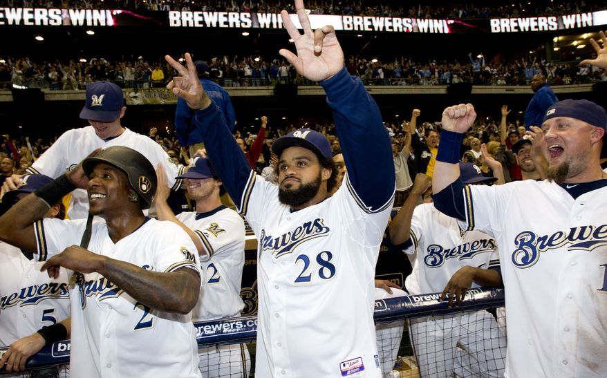 Milwaukee Brewers' Nyjer Morgan (2), Prince Fielder (28) and Casey McGehee react as they watch the end of the Cardinals Cubs game after a baseball game against the Florida Marlins, Friday, Sept. 23, 2011, in Milwaukee. The Brewers clinched a NL Central title with a win over the Marlins 4-1. (AP Photo/Morry Gash)