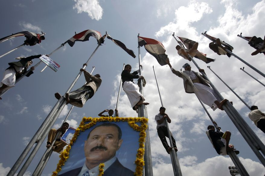 Supporters of Yemen's President Ali Abduallah Saleh stand on flag poles celebrating his return to Sanaa, Yemen, Friday, Sept. 23, 2011. Saleh made a surprise return to Yemen on Friday after more than three months of medical treatment in Saudi Arabia in a move certain to further inflame battles between forces loyal to him and his opponents that have turned the capital into a war zone. (AP Photo/Hani Mohammed)