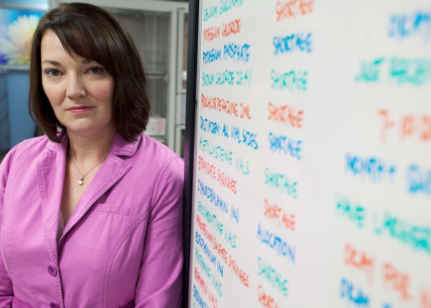 """Erin Fox, manager of the Drug Information Service at the University of Utah Hospital in Salt Lake City, stands by a board listing drugs in short supply. """"The shortages aren't resolving. They're piling up on top of existing ones,"""" she said. (Associated Press)"""