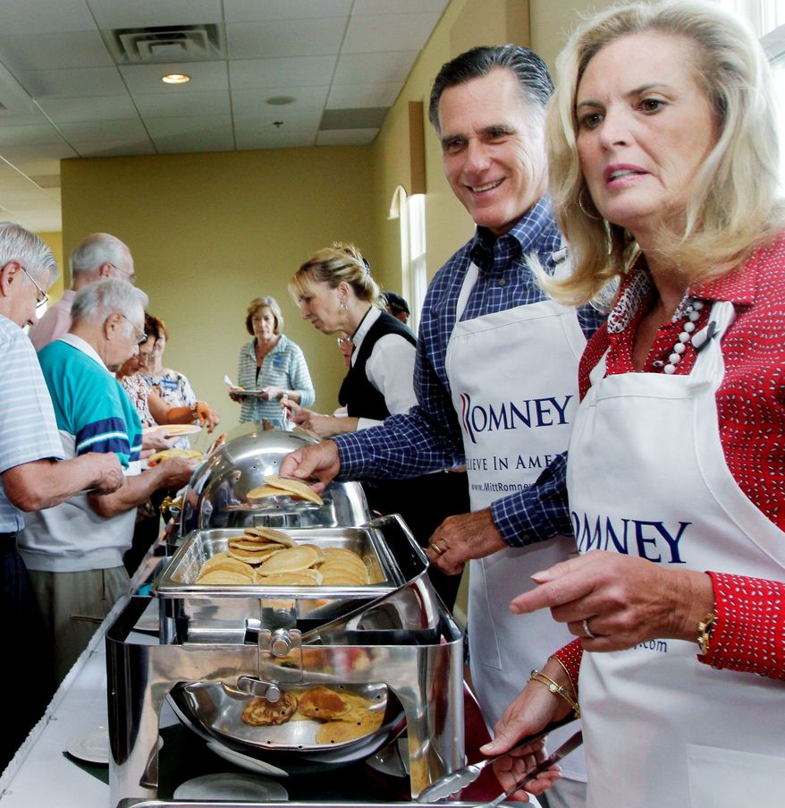 """Former Massachusetts Gov. Mitt Romney, a Republican presidential candidate, and Ann, his wife of 42 years, serve up a Labor Day pancake breakfast in Manchester, N.H., She wears the white apron with the ease of a woman who spent countless mornings flipping flapjacks for five hungry sons. """"It's going to happen this time,"""" she said. (Associated Press)"""