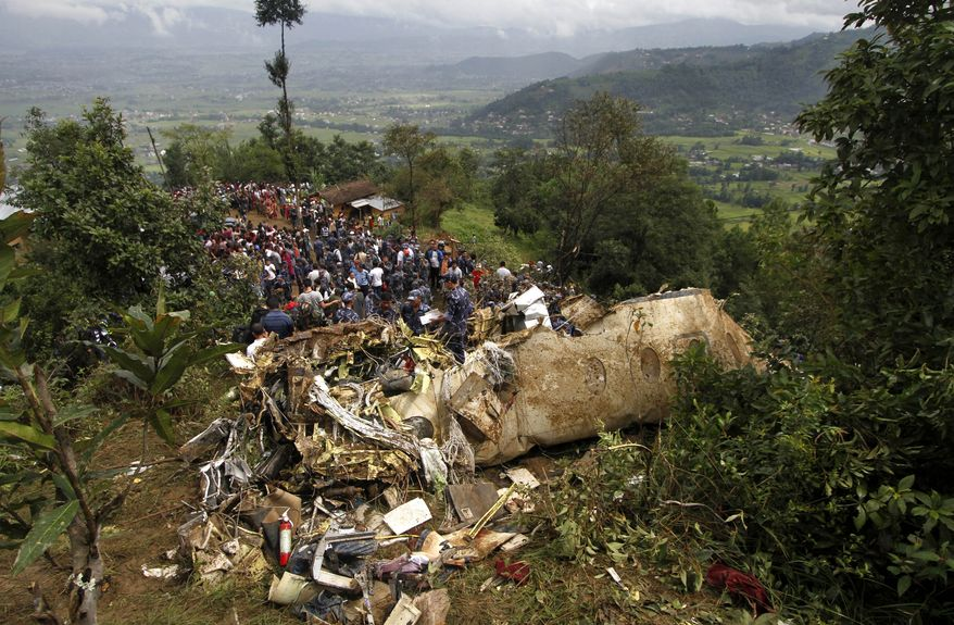 Nepalese rescue workers and civilians gather around the wreckage of a Beechcraft 1900D operated by Buddha Air after it crashed in the mountains outside Bisankunarayan village, just south of Katmandu, Nepal, on Sunday, Sept. 25, 2011. The plane, carrying tourists to view Mount Everest, went down while attempting to land in dense fog; all 19 people on board were killed, officials said. (AP Photo/Niranjan Shrestha)