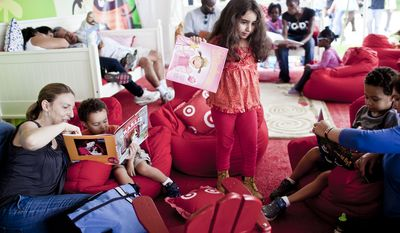 Kerri DiZoglio, left, of Takoma Park, Md., reads to her son Alec Barrera, 2, as her son Jaeden Barrera, 4, reads with Theresa Bosanek, at right, while Julia Brunetti, 6, center, of Bethesda, Md., gets up to find a new book in a family storytelling tent at the National Book Festival.(T.J. Kirkpatrick/ The Washington Times)