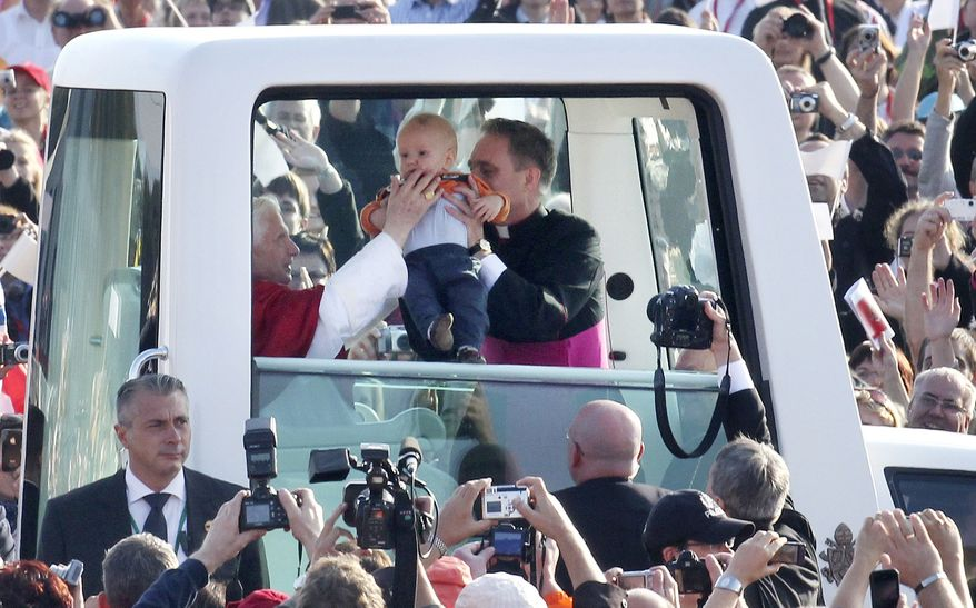 Pope Benedict XVI touches a baby as he drives through the crowd in his popemobile before celebrating Mass in Freiburg, Germany, on Sunday, Sept. 25, 2011, the last day of a four-day visit to his homeland of Germany. (AP Photo/Michael Probst)