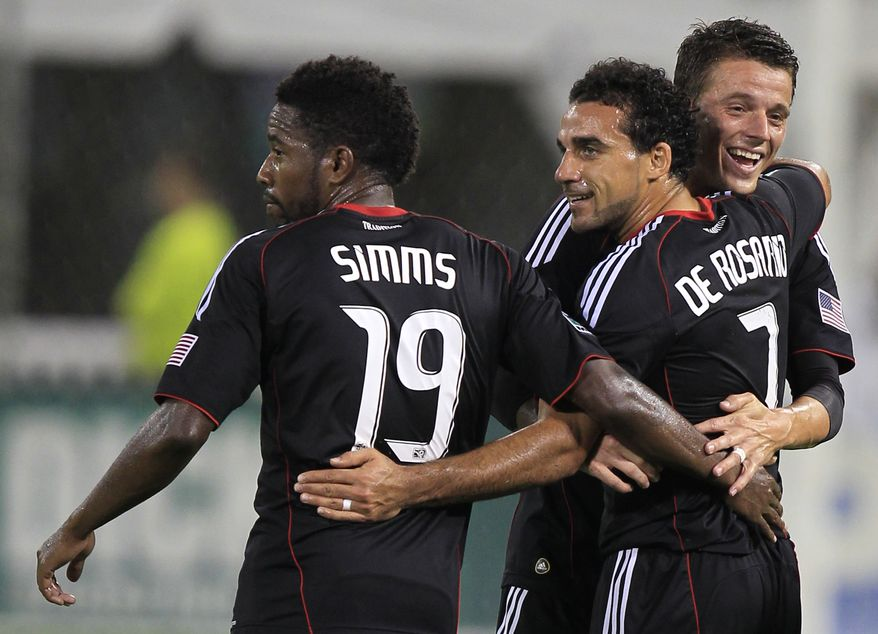 D.C. United's Dwayne De Rosario celebrates with teammates Clyde Simms and Marc Burch after scoring a goal on a free kick during the first half against Real Salt Lake on Saturday, Sept. 24, 2011, in Washington. De Rosario became the fastest player in MLS history to record a hat trick, reaching the feat by the 31st minute. (AP Photo/Luis M. Alvarez)