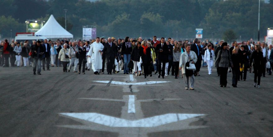 Pilgrims walk to a mass with Pope Benedict XVI on the tarmac of the airport in Freiburg, southwestern Germany.  (AP Photo/Matthias Schrader)