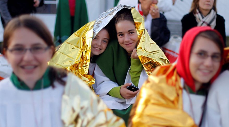 Altar girls protect themselves against the cold with rescue blankets as they walk to a mass with Pope Benedict XVI in Freiburg, southwestern Germany.  (AP Photo/Matthias Schrader)