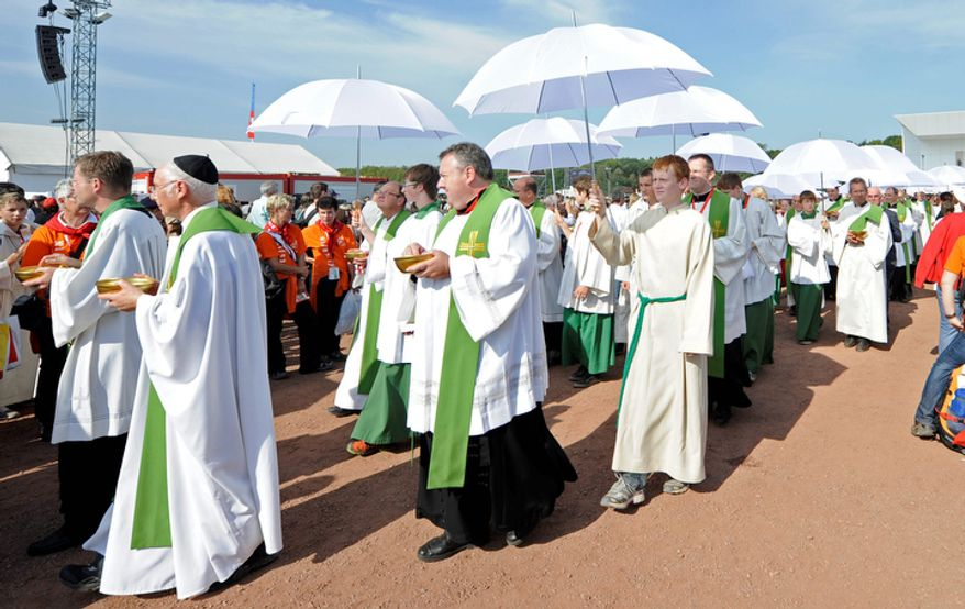 Priests prepare the communion at a mass with Pope Benedict XVI at the airfield in Freiburg, Germany. (AP Photo/Martin Meissner)