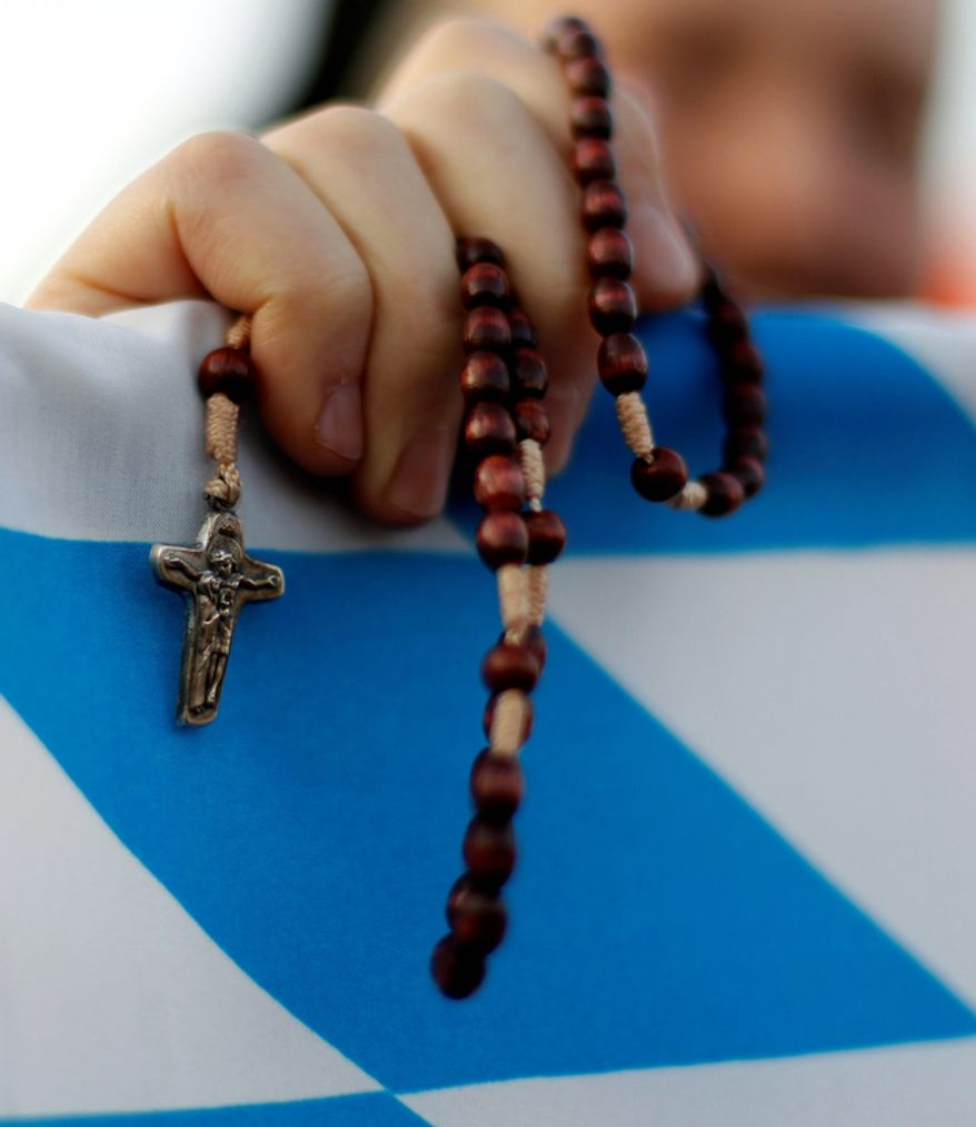 A nun holds a rosary as she waits of the beginning of a mass with Pope Benedict XVI  in Freiburg, southwestern Germany, Sunday, Sept. 25, 2011. (AP Photo/Matthias Schrader)
