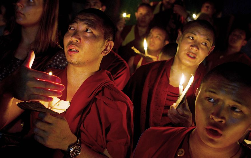 """Exiled Tibetan monks hold a candlelight vigil in Dharmsala, India, as they react to news reports of self-immolation by two Tibetan monks at the Kirti Monastery in China's Sichuan province. The two monks, who are in stable condition after being rescued by police, called out """"long live the Dalai Lama,"""" according to Free Tibet. (Associated Press)"""
