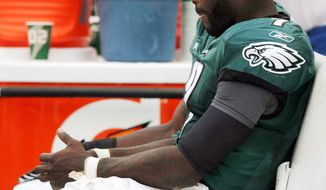 Eagles quarterback Michael Vick injured his right hand Sunday, and his status for this week's game against San Francisco is uncertain. (Associated Press)