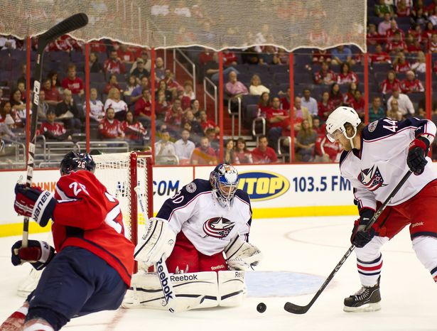** FILE ** Goaltender Curtis Sanford of the Columbus Blue Jackets blocks a shot on goal by Matt Hendricks (left) of the Washington Capitals in the second period of a preseason game at the Verizon Center in Washington on Monday, Sept. 26, 2011. (Andrew Harnik/The Washington Times)