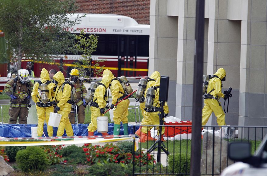 A Hazmat team enters the Chemistry Building on the University of Maryland campus in College Park on Monday after an explosion and small fire injured two students in a lab. (Associated Press)