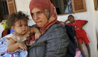 Samia Tahir, a U.S. citizen from Illinois who lived in Tawarga, Libya, holds her daughter while waiting to be rescued along with other internally displaced Libyans outside Sirte, the hometown of Col. Moammar Gadhafi, on Monday, Sept. 26, 2011. (AP Photo/Bela Szandelszky)