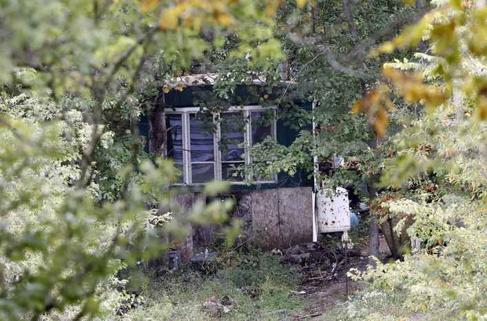 On Monday, Sept. 26, 2011, trees and brush surround the mobile home where four people were found dead Sunday near Laurel, Ind., in rural Franklin County. A fifth person was found dead across the road. (AP Photo/A.J. Mast)