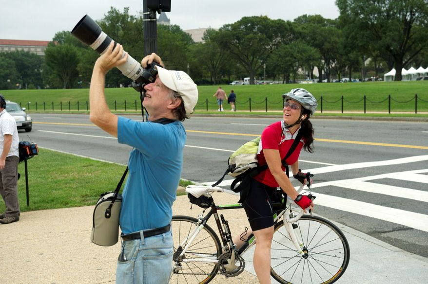 Patti Hurst of Arlington and Jeff Malet of the District check out the efforts of the Washington Monument damage assessment team. (Rod Lamkey Jr./The Washington Times)