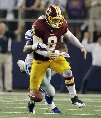 Dallas Cowboys linebacker Anthony Spencer forces Washington Redskins quarterback to fumble (which was recovered by the Cowboys) late in the fourth quarter to seal Dallas' 18-16 victory over the Redskins. (AP Photo/Tony Gutierrez)