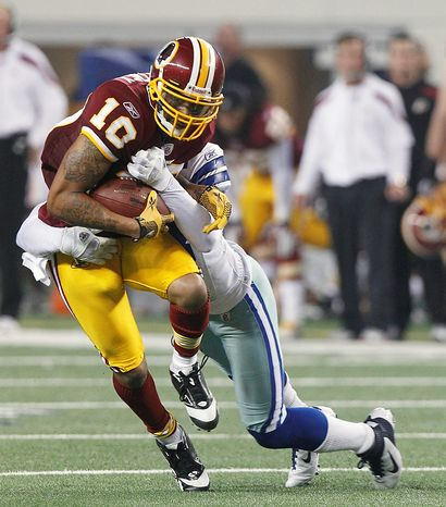 Washington Redskins wide receiver Jabar Gaffney is tackled by Dallas Cowboys free safety Gerald Sensabaugh during the first half of an NFL football game Monday, Sept. 26, 2011, in Arlington, Texas. (AP Photo/LM Otero)