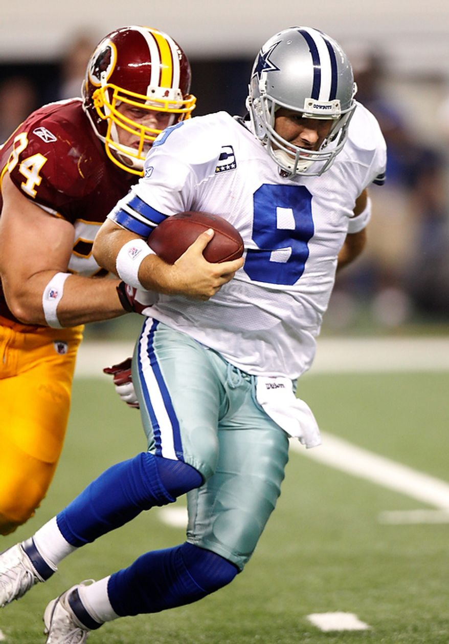 Washington Redskins defensive end Adam Carriker tackles Dallas Cowboys quarterback Tony Romo during the second half of an NFL football game Monday, Sept. 26, 2011, in Arlington, Texas. (AP Photo/LM Otero)