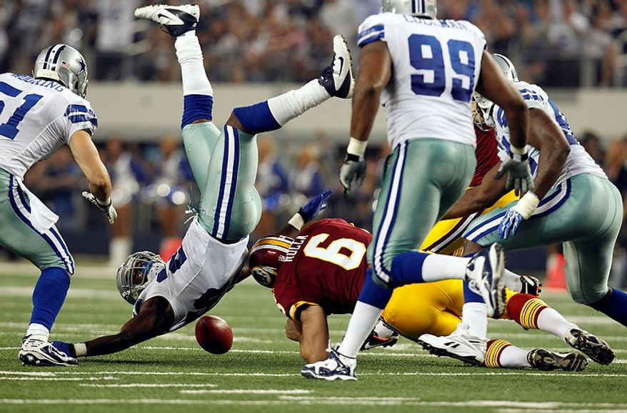 Players spill over after Dallas Cowboys' Gerald Sensabaugh blocked a field goal attempt by by Washington Redskins kicker Graham Gano during the first half of an NFL football game Monday, Sept. 26, 2011, in Arlington, Texas. Washington holder Sav Rocca (6) and others scramble for the ball. (AP Photo/LM Otero)